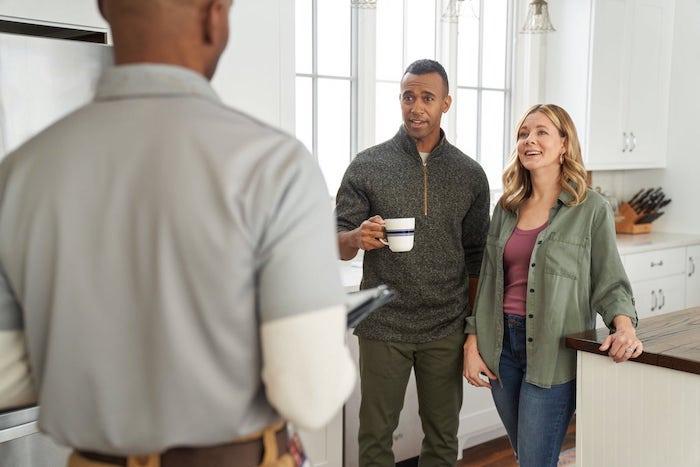 Homeowners talk to appliance repairman