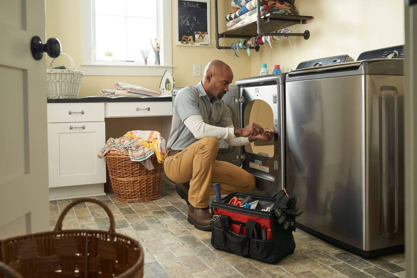 Appliance Repairman repairs dryer