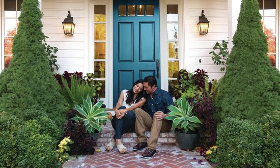 Homeowners in front of blue door