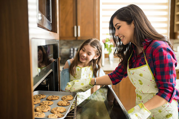 Mom and child baking cookies in oven