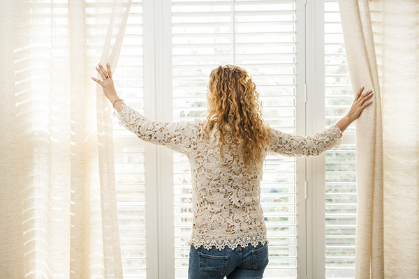 Woman looking out of window with blinds