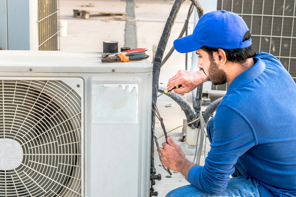 Technician in blue working on a/c