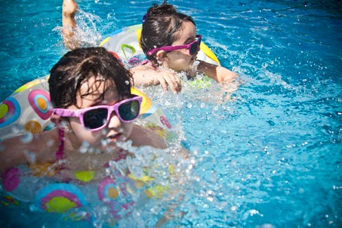 Children swimming with flotation devices