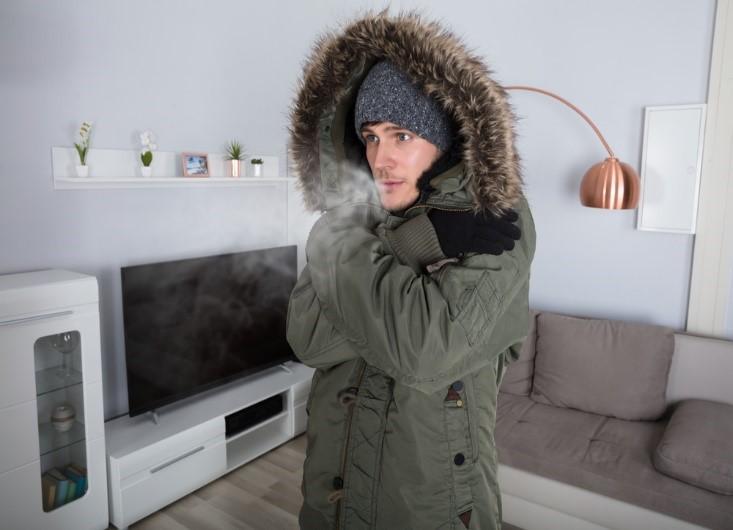 Cold man wearing coat inside home