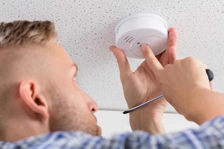 Homeowner inspecting smoke detector
