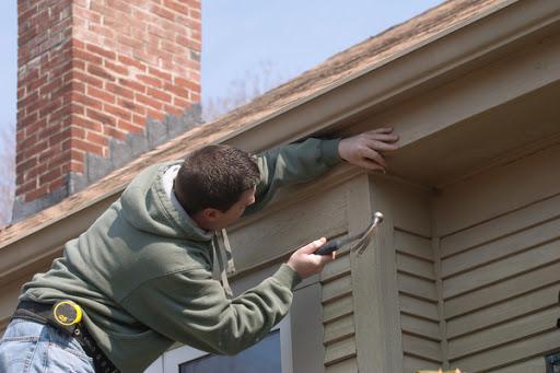 Man fixing siding of house
