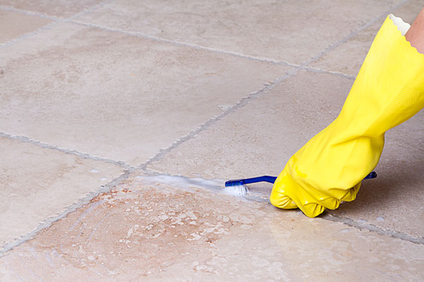 Someone Cleaning Grout with Toothbrush