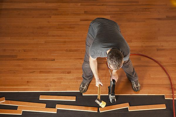 Man installing hardwood floor planks