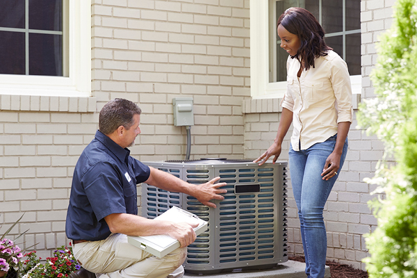 Technician helping with outdoor AC unit