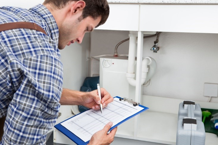 Homeowner checking maintenance checklist