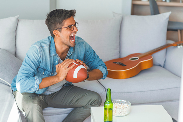 Man holding football in man cave