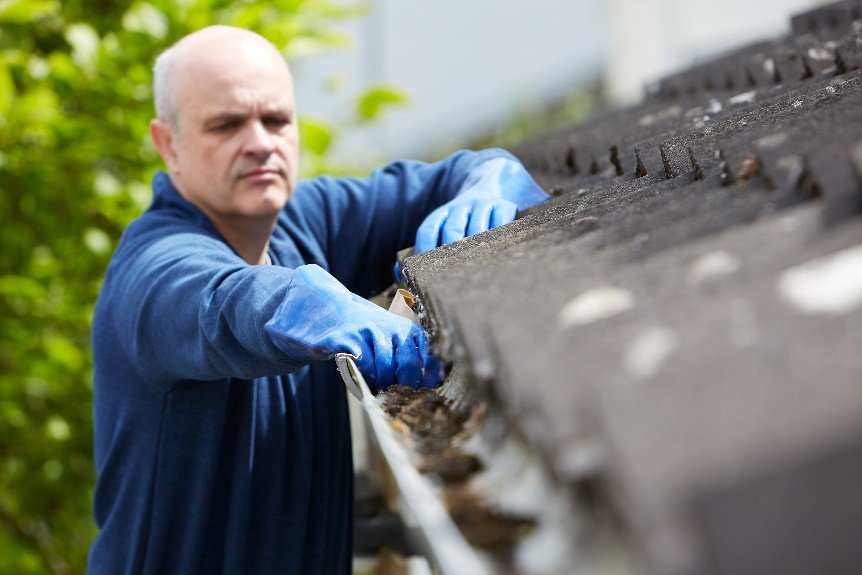 Man cleaning out the gutters
