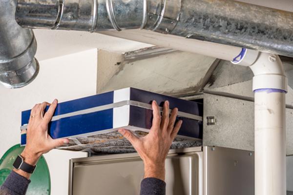 Man replacing furnace in home