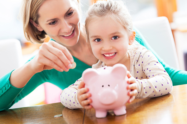 Young girl holding money bank