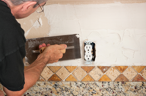 Man tiling a backsplash in kitchen