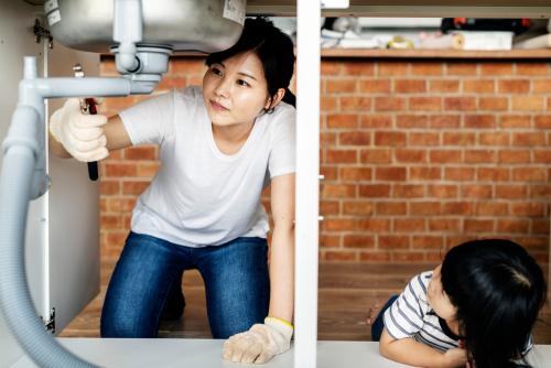 Woman checking plumbing under sink