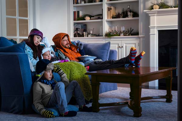 Family Sitting on Couch Bundled up Because of a Broken Heater
