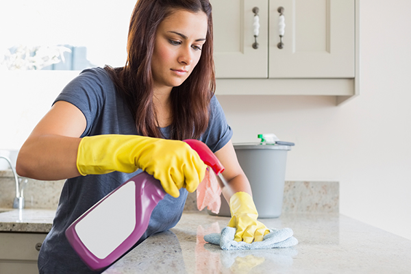 Woman Cleaning Kitchen Attempting to Ward off Flu