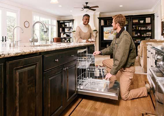 Man Talking to Woman While Loading Dishwasher