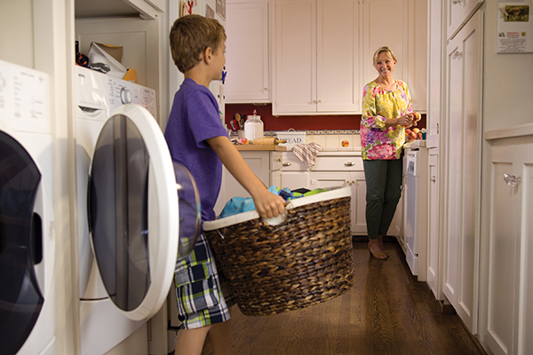 Young Boy with Laundry Basket Standing In front of Washer