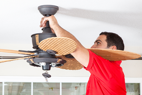 Male Installing Ceiling Fan to Conserve Energy Usage