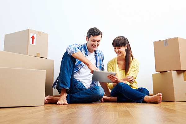 Couple Surrounded by Boxes Looking for Professional Movers on iPad