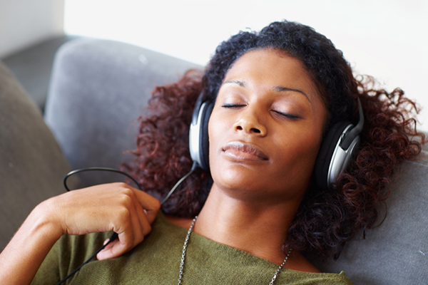Woman Wearing Over the Ear Headphones Listens to Music to Relieve Stress
