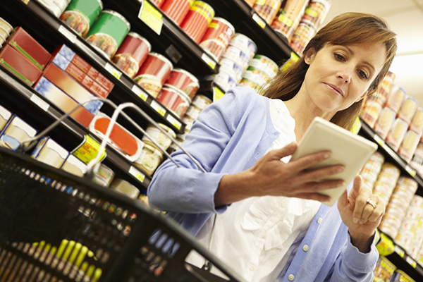 Woman at Grocery Store Looks Through Grocery List on Smart Device