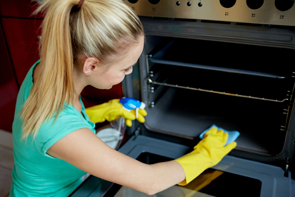 Woman Cleans Inside Oven