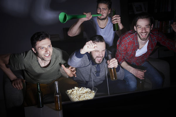 Four Males Enjoying a Football Game on TV in a Man Cave
