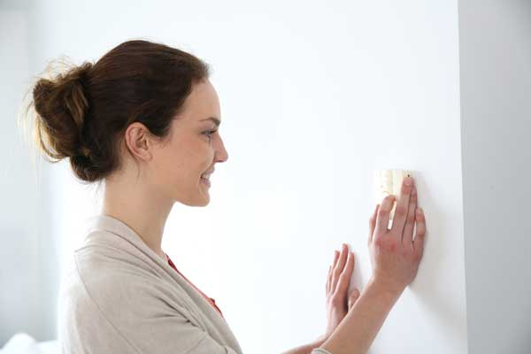 Woman Adjusts Home Thermostat