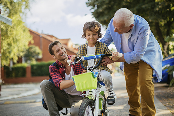 Father and son helping young boy on bike