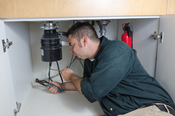 Repair man fixing a garbage disposal