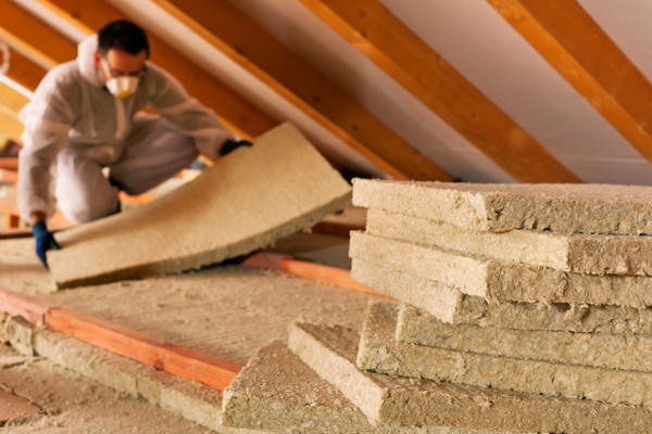 Technician laying insulation in attic space