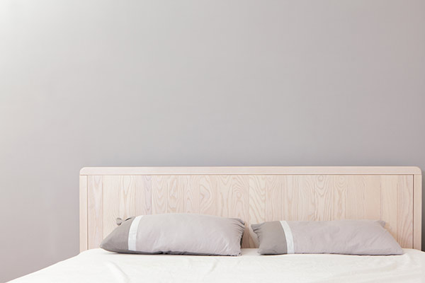 Neautral Bed Frame and Bed in Front of Gray Wall