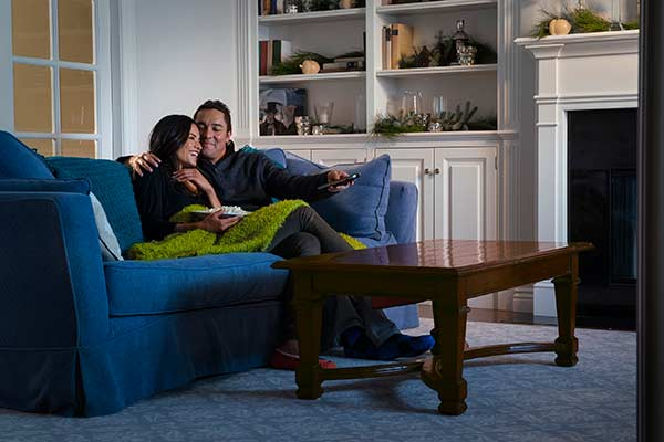 Couple Sitting on Living Room Couch Trying to Survive Winter